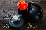 Kettle bell with shaker, scoop of protein and vitamins, close-up