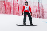 young athlete male snowboarder during competition goes down on mountain slope