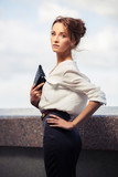 Young fashion business woman with handbag walking on city street