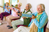 Fototapety Cheerful senior women exercising their arms.