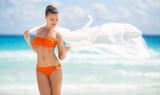 Beautiful woman on the beach in orange bikini