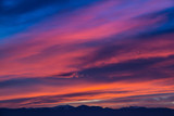 Sunset / sunrise with vivid magenta sky, clouds and mountains dark silhouettes.