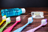 Set of colorful toothbrush with mouthwash and dental floss on wooden board