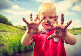 Child playing outdoor showing dirty muddy hands. - 102774892