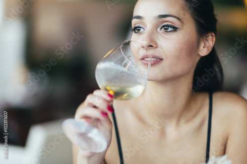 Poster Attractive woman tasting white wine