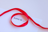 Paper with words Love is and ribbon