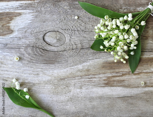 Fotobehang Lelietjes van dalen Decorative border or frame with lily of the valley flowers on a wooden background. Photo from above.
