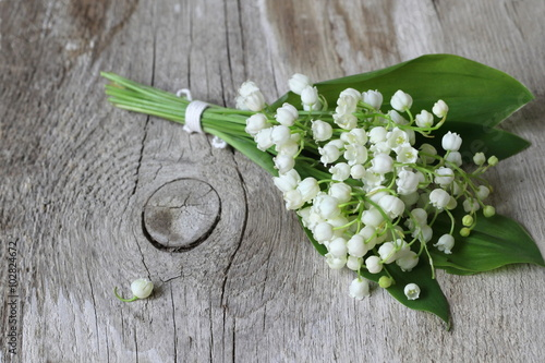 Bouquet of spring flowers Lily of the valley lying on a wooden plank.
