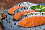 Fresh salmon portions with herb and pepper seasoning.