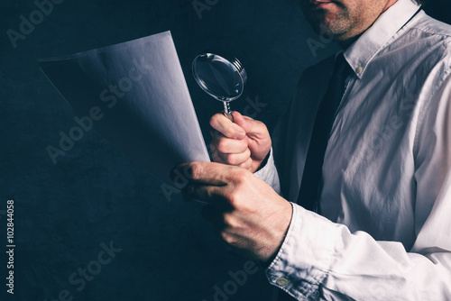 Tax inspector doing financial auditing, businessman reading business report or contract footnotes disclaimer with magnifying glass, retro toned, selective focus
