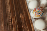 packaging white eggs with one egg rouged on the wooden table