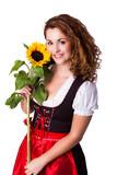 junge brünette Frau im Dirndl mit Sonnenblume