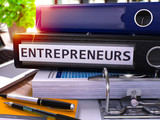 Black Office Folder with Inscription Entrepreneurs on Office Desktop with Office Supplies and Modern Laptop. Entrepreneurs Business Concept on Blurred Background. Entrepreneurs - Toned Image. 3D.