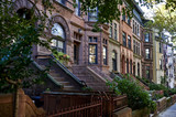 a row of brownstone buildings poster
