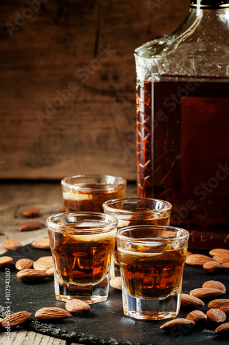 Cold whiskey with ice in a glass and a snack almonds, selective