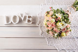 Beautiful wedding bouquet of roses and freesia with letters on white wooden background, background for valentines or wedding day