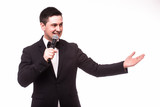 Young elegant talking man holding microphone and present invisible product. Isolated on white.Showman concept.