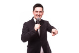 Young elegant talking man holding microphone talking with pointing finger. Isolated on white background. Showman concept.