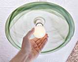 Hand twists energy-saving LED lamp on ceiling light.