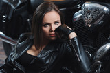 Portrait of a girl in a leather jacket near a motorcycle