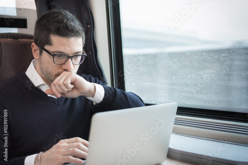 man working with computer on a train Poster