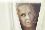Sad beautiful woman looking out window