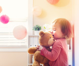 Fototapety Happy toddler girl playing with her teddy bear