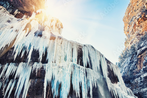 Fototapeta Frozen waterfall in the mountains at sunset.