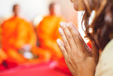 The woman praying while religious ceremony with monk background