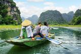 Fototapety Tourists in boat. Rower using her feet to propel oars, Vietnam