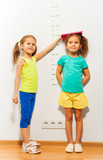 Little girl help friend to measure height on scale