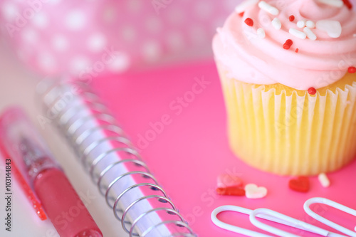 A frosted pink cupcake on a pink notebook with paperclips, a pen, and a ribbon. - 103144843