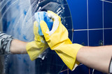 Cleaning - Hand in a yellow rubber glove washing the glass in the bathroom