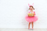 Fototapety Happy child girl in a costume Easter bunny rabbit with basket of