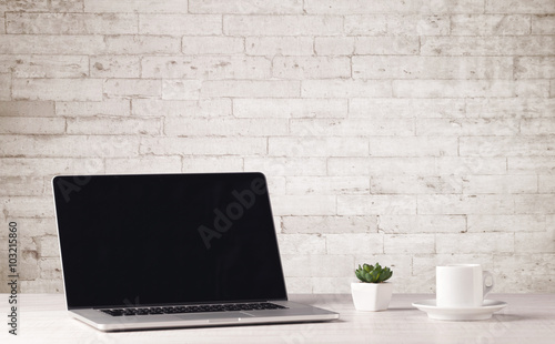 Business laptop with white brick wall