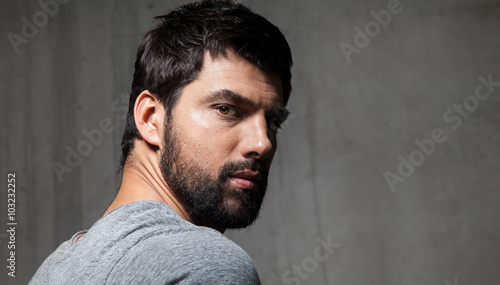 Portrait of handsome bearded guy from behind on a background of a cement wall