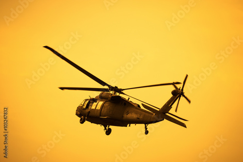 Poster Silhouette of the military helicopter  moving into sky at sunset