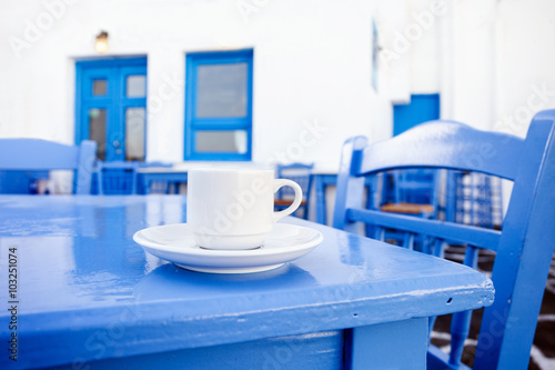 A cup of coffee on table with Greek street at the background