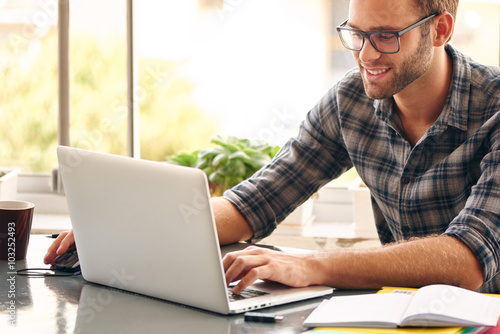 Happy man sitting and working at his desk from home