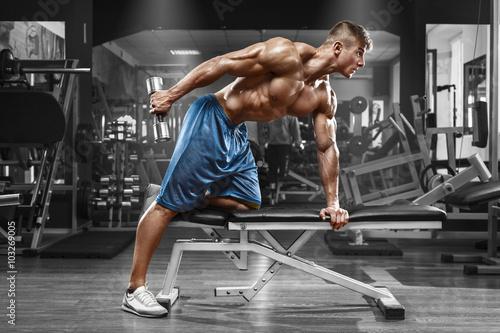 miesniowy-mezczyzna-pracujacy-w-gym-robi-cwiczeniom-z-dumbbells-przy-triceps-out-silny-meski-nagi-polpostaci-abs