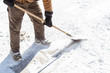 man scraping ice with shovel