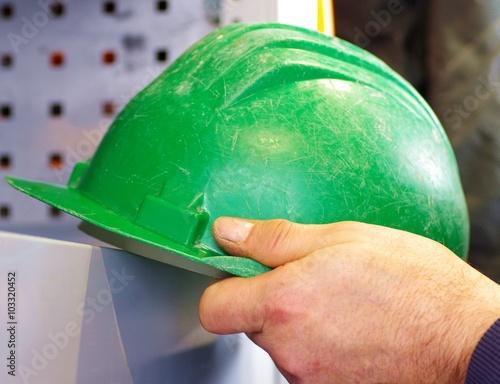 Poster Handwerker hält grünen Sicherheitshelm in der Hand