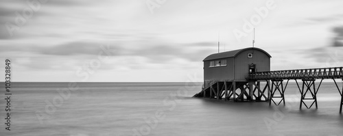 Beautiful long exposure landscape image of jetty at sea