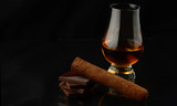 Glass with whisky isolated over a black background