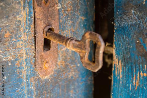 Vieux clé rouillée et serrure sur une porte en bois bleu Poster