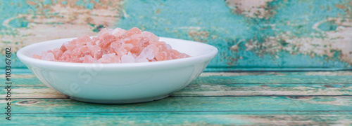 Himalaya or Himalayan rock salt in wooden bowl over wooden background