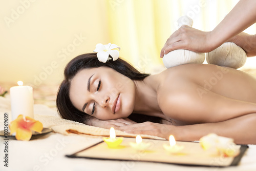 Poster Young woman getting massage in Thai spa.