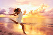 Leinwanddruck Bild Freedom wellness well-being happiness concept. Happy carefree Asian woman feeling blissful jumping of joy on peaceful beach at sunset. Serenity, relaxation, mindfulness, stress free concepts.