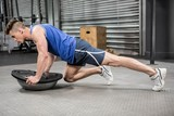 Muscular man doing push up on bosu ball