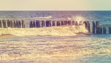Retro stylized picture of wave crashing against wooden posts
